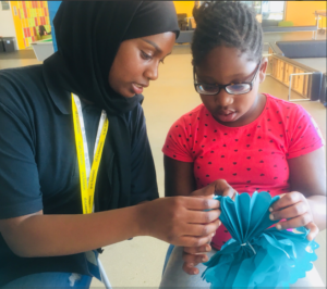 volunteer helping young person with art