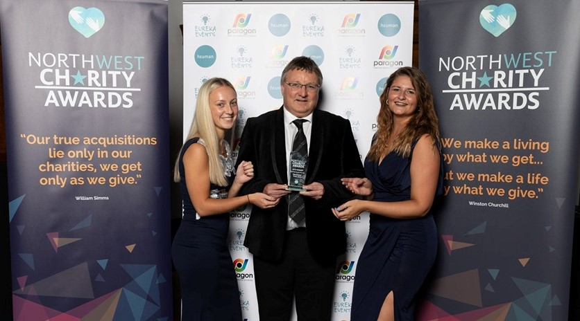 Manchester Youth Zone CEO, Richard March, and staff Lucy and Kirsty receiving the Charity of the Year trophy at North West Charity Awards 2019